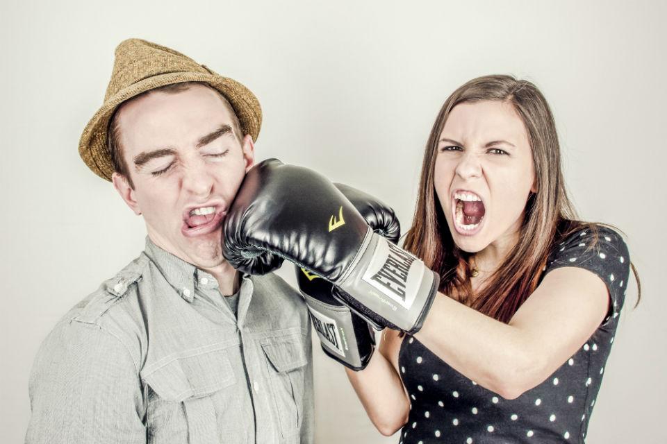 Imagen de una mujer golpeando a un hombre con un guante de boxeo