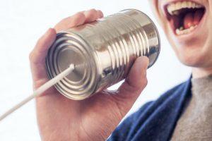 Imagen de un hombre hablando en un teléfono hecho con lata y cordel