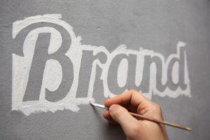 Imagen de una pizarra donde una mano escribe Brand