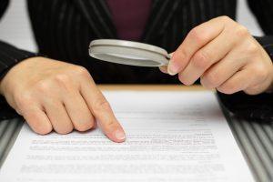 hombre revisando con lupa la letra pequeña crear nombres de marca y su proteccion juridica